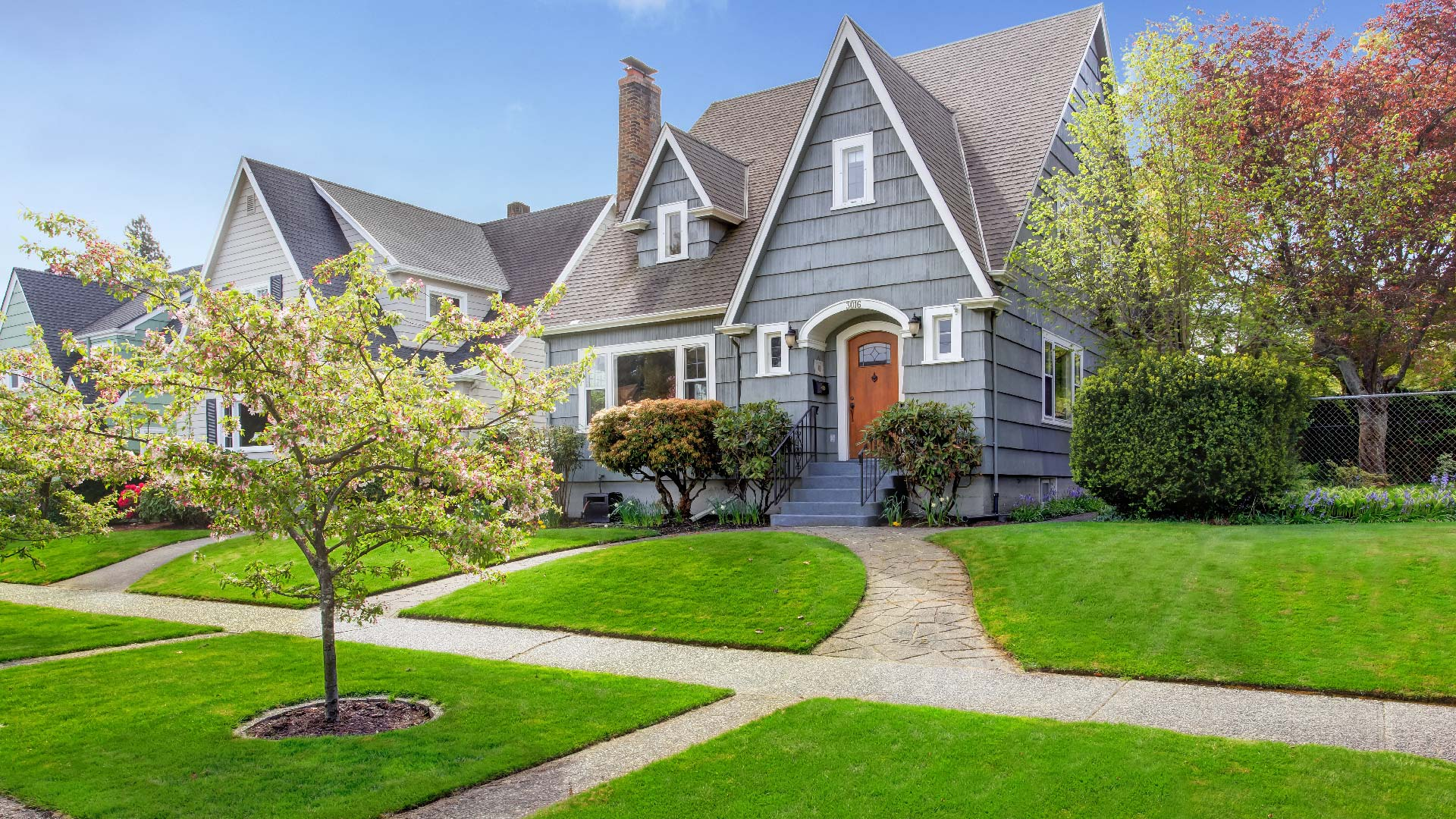gray house with perfect front yard lawn
