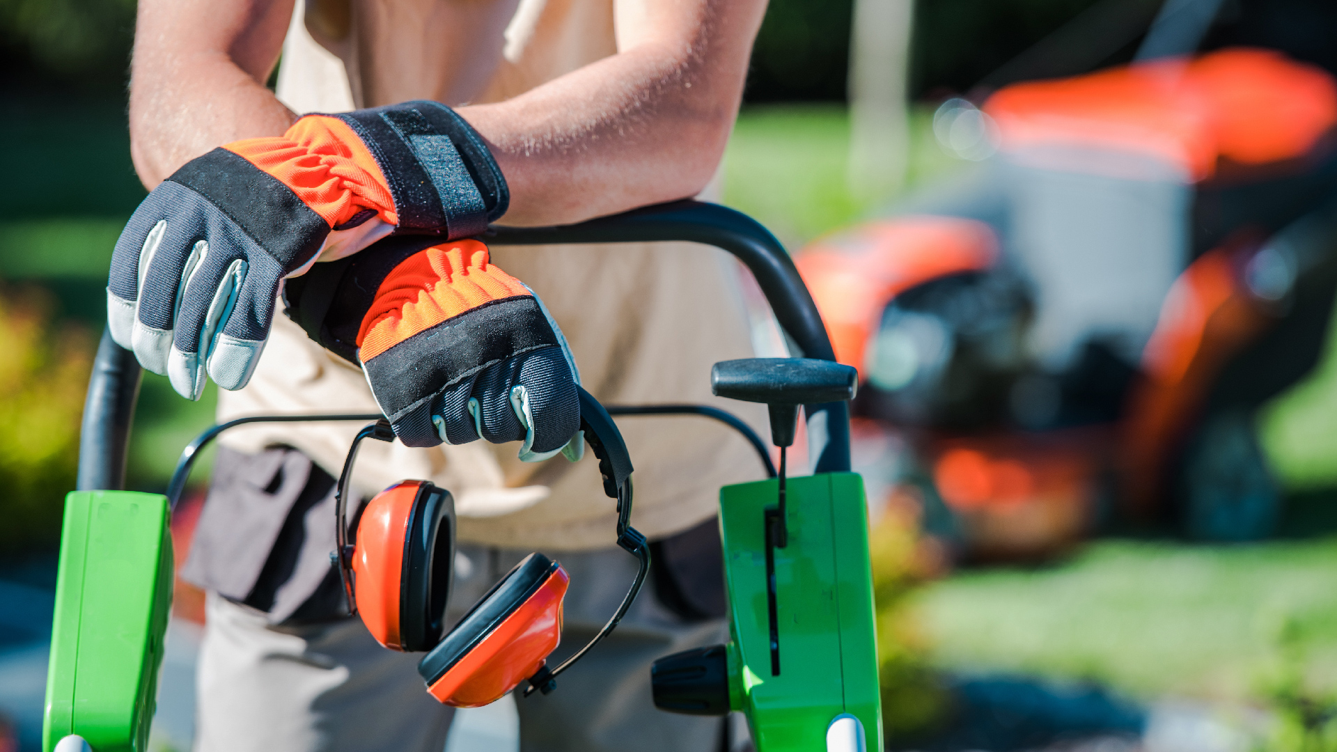 man wearing safety gloves holding ear protection leaning on lawn mower