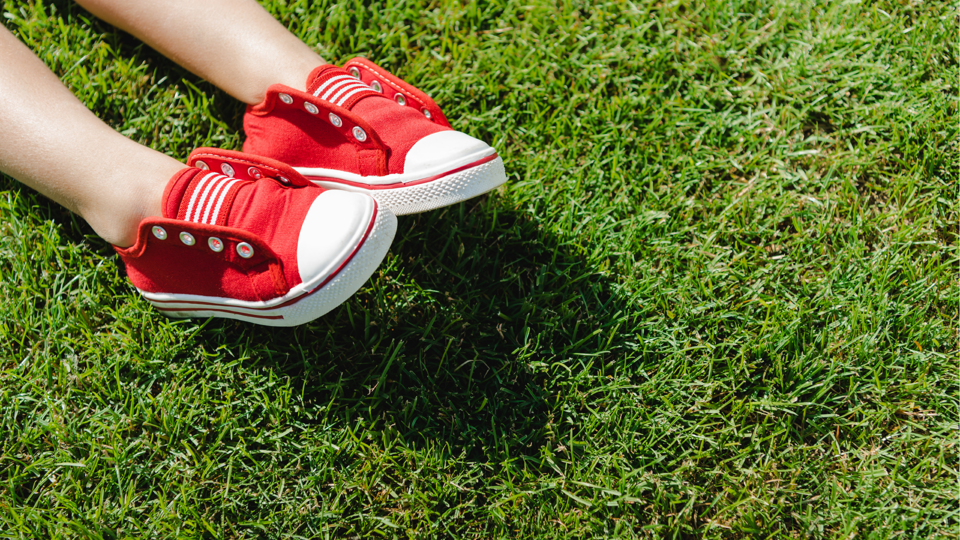 child's legs and red shoes on green grass